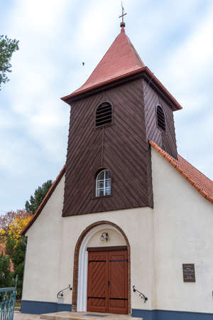 A village church in Falkensee, Germany with a wooden tower and a central entrance by day. Redakční