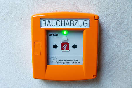 Berlin, Berlin/Germany - 03.09.2019: An orange manual call point for fire and smoke extraction in case of fire with a green LED indicating that the detector is ready in a hotel.