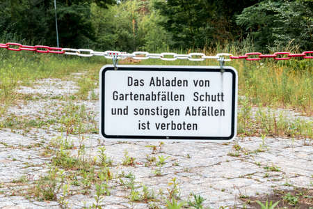 Berlin, Berlin/Germany - 19.07.2019: A sign, hung on a red and white chain in front of an empty square, stating that the dumping of garden waste, rubble and other refuse is prohibited.