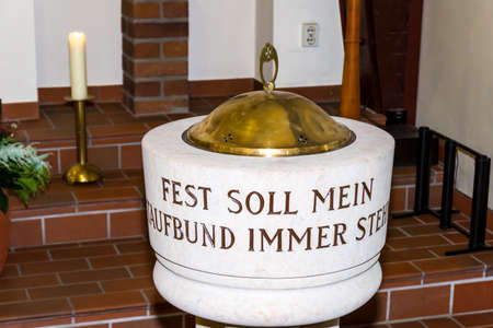 Berlin, Berlin/Germany - 03.11.2018: A white baptismal font with a metal lid and the inscription