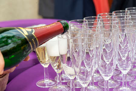 Berlin, BerlinGermany - 03.11.2018: With a champagne bottle champagne is filled into different champagne glasses, you see a lot of foam, full and empty glasses for a champagne reception. Redactioneel