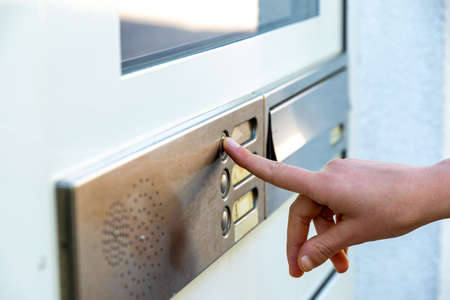 Berlin, Berlin/Germany - 03.09.2019: A finger pressing a metal front door bell with several buttons on a front door where an intercom system is also installed
