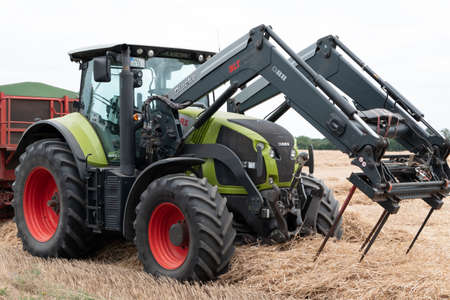 Berlin, Berlin/Germany - 11.07.2019: A green tractor of Claas with hay fork in front standing on a field with hay from diagonally in front photographed.