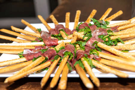 Berlin, Berlin/Germany - 03.11.2018: A plate with finger food, consisting of pastry sticks wrapped in salad and ham and arranged in a star shape. Redakční