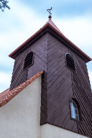 A wooden bell tower that stands on top of a brick-built church with windows and a weather vane under a beautiful blue sky during the day.