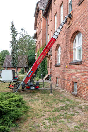 Berlin, Berlin/Germany - 19.07.2019: A red furniture elevator on a house wall, which allows furniture to be easily transported from the ground floor to a higher floor during a move. Redakční