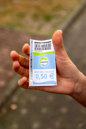 Berlin, Berlin/Germany - 03.09.2019: A ticket or voucher in hand from the company Sanifair, a toilet payment system at motorway service areas in Germany with a printed price of fifty cents.