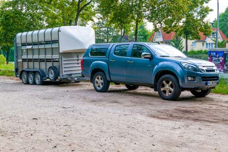 Berlin, Berlin/Germany - 06.08.2019: A horse trailer with three axles and an off-road vehicle coupled as a towing vehicle ready for departure. Redakční