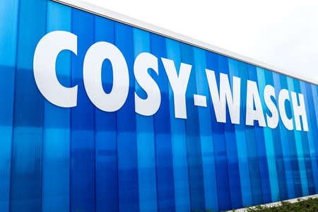 Berlin, Berlin/Germany - 12.07.2019: The facade of the car wash of Cosy-Wasch in Falkensee with the white writing on a blue background