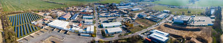 Zeestow, Brandenburg/Germany - 26.03,2020: The industrial area in Zeestow Brandenburg photographed from the air as a panoramic picture with factory buildings, solar field and individual company sites.