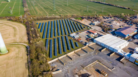 Zeestow, Brandenburg/Germany - 26.03,2020: A solar field for power generation next to an industrial area in sunshine.