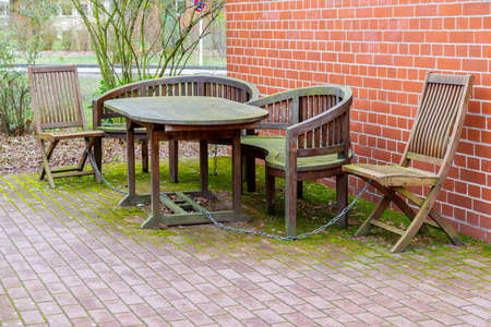 A wooden seating group, consisting of a wooden table, wooden chairs and a wooden bench in front of a house wall, chained against theft and covered with a green layer of algae, moss and lichen, just like the paved floor.