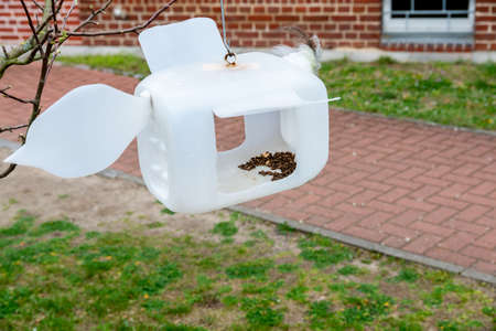 A bird house made of a white plastic canister into which openings were cut, it was hung up and filled with bird food. Reklamní fotografie