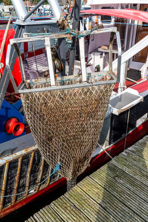 A fishing net on an old fishing boat at the Baltic Sea for lifting for larger catches and fish with traces of rust and remains of paint.