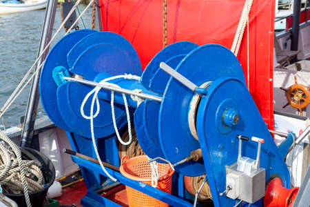 A blue winch with lines on a small fishing boat for hauling in trawl nets with control lever and steering wheel.