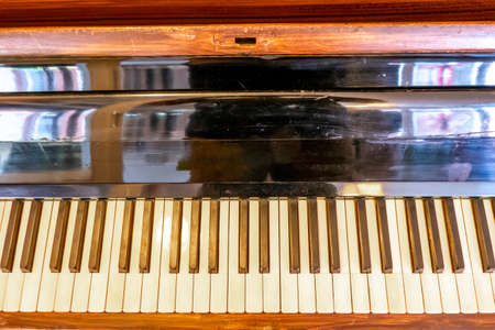 The middle part of an old brown piano with the foldable music stand and the middle part of the keyboard with the white and black keys.