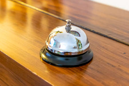 A chrome-plated table bell or reception bell with black base on a wooden surface that reflects and shines in the light Stock Photo