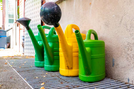 Four used garden watering cans in green and yellow, standing on a grid and on a house wall, to which two watering nozzles are attached.