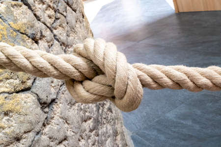 A rope made of natural fibre, which is used as a barrier rope, tied to a natural stone wall with a knot in the middle.