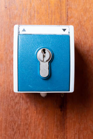 A blue key switch with cylinder screwed to a wooden wall with the symbols up and down to operate a switching operation with a key.