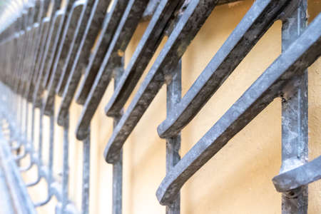Wrought-iron work on a yellow wall for protection and decoration made of moulded rods welded together.