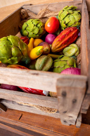 A wooden box decorated with various vegetables and fruits made of plastic or plastic, including mango, star fruit artichoke and banana in bright colors. Reklamní fotografie