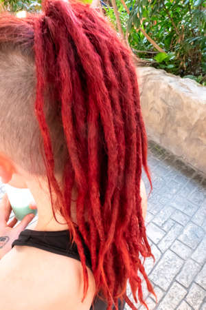 Red dreadlocks of on the back of a girl's head, with the rest of her hair almost shaved off, walking on a sidewalk. 写真素材