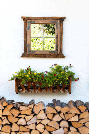 A decorative window on a house wall over a flower box and firewood, which gives a nice picture from the street