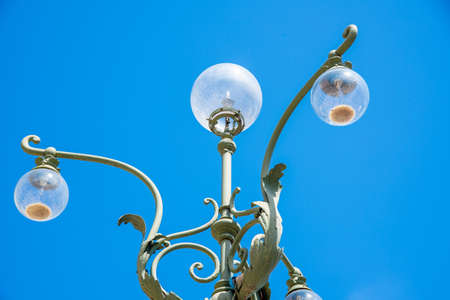 A street lamp in Verona, located in the historic center, artistically adorned with wrought-iron figures and forms and yet operated with halogen light, photographed against a blue sky.