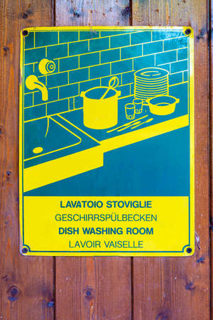 A green-yellow plastic sign with the reference in pictograms and different languages to a dishwasher so that guests can wash the dishes. Reklamní fotografie