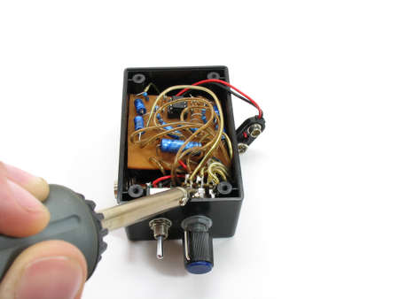 Soldiering a wire in place on a homemade microphone amplifier. An Electronics project.