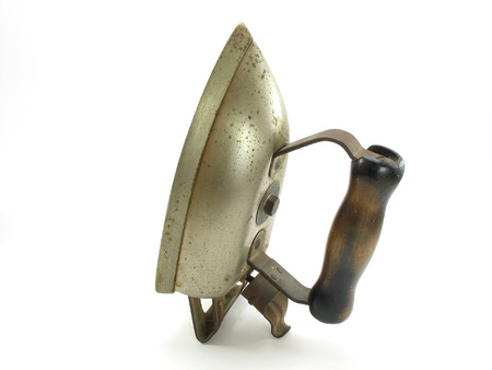 An antique electric clothes iron. Well worn with rust and pits. The wooden handle also shows this model was in heavy use at one time. Zdjęcie Seryjne