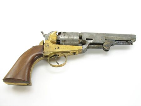 black powder: A black powder pistol. This antique revolver has wooden grips and brass trimmings. It shows its age with dents and damage but still makes for an interesting item.