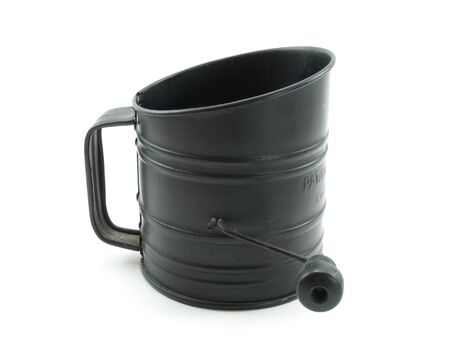 sifter: This is an antique black tin flour sifter. Hand cranked from the right hand side. This one has weathered the years quite well. Stock Photo