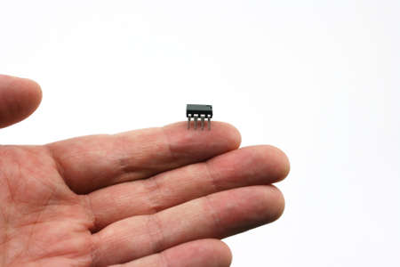 An isolated on hand on a white background holding a micro chip on the finger tip.