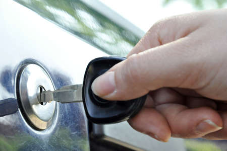a hand puts a key in the lock of a car