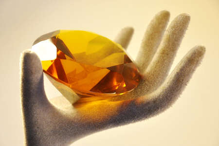 hardness: amber diamond resting on a hand used to display jewelry Stock Photo