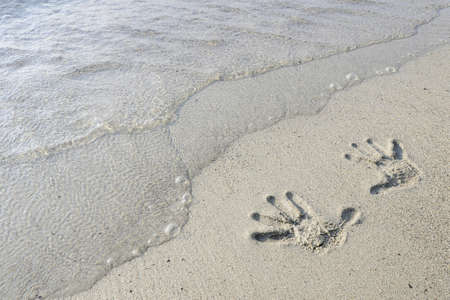 fingerprints of two hands in the sand on the seashore