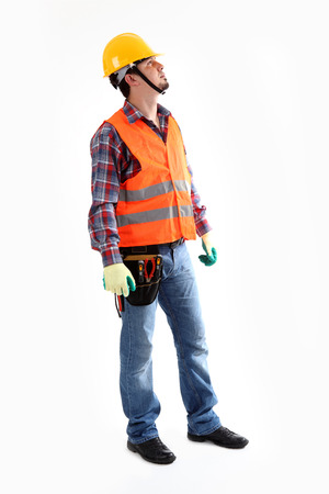 Serious construction worker in yellow helmet and orange waistcoat looking up  Full length studio shot isolated on white Stock Photo - 31000416