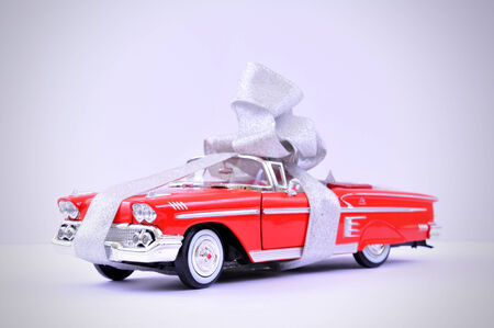 A ribbon wrapped undefinable model car as a gift.
