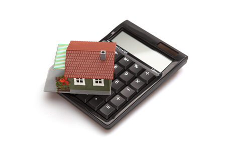 downpayment: A house on top of a calculator isolated on a white background