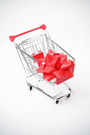 Shopping cart with big red bow on the white background  photo