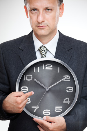 Business time. Businessman looking at his imaginary wristwatch worrying, being late concept. photo