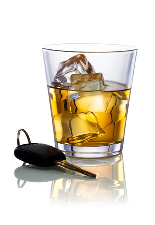 A shot of whiskey and a set of car keys on a white background. photo