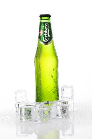 carlsberg: A 0.33 liter bottle of cold Carlsberg beer sweating drops of water, isolated on white background. Carlsberg is a pale lager (pilsner) beer that originates in Denmark, first brewed in 1904.
