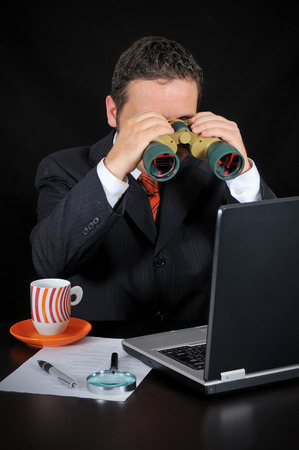 Businessman is Researching with binoculars on the black background photo