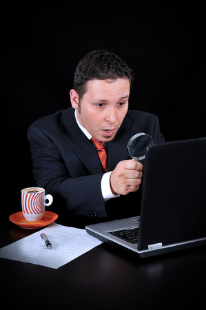 stunned businessman on the computer on the black background photo