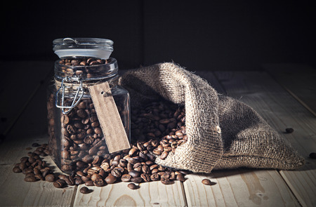 Coffe beans out a sack and jar photo