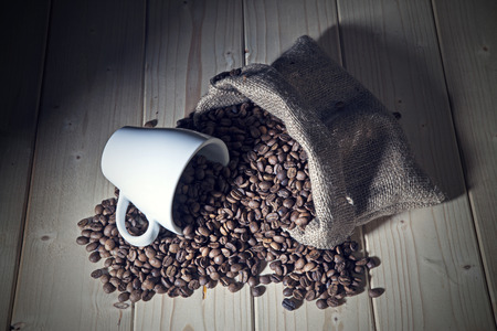 Burlap sack full of coffee beans with white mug photo