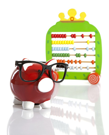 Abacus sits behind a red bank showing calculation of savings photo